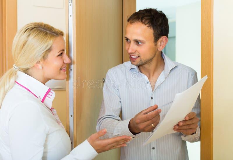 Man en vrouw met documenten bij deuropening stock afbeelding