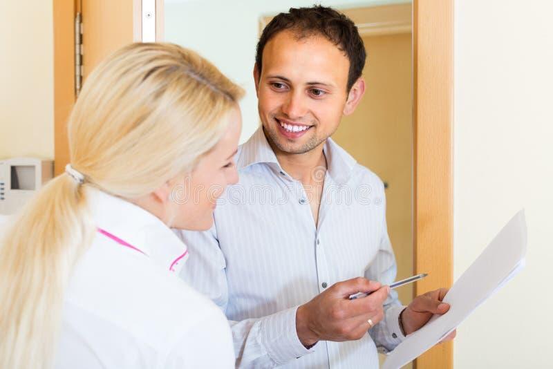 Man en vrouw met documenten bij deuropening stock afbeeldingen