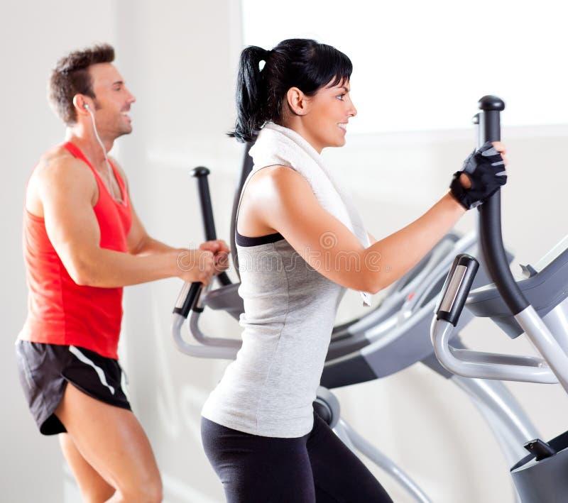 Man en vrouw met elliptische dwarstrainer bij gymnastiek stock foto