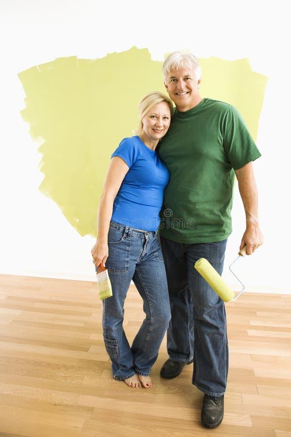 Man en vrouw met helft-geschilderde muur. stock foto's