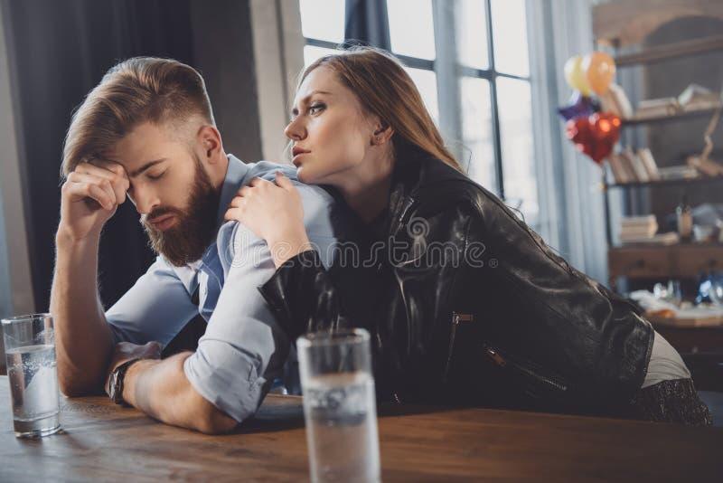 Man en vrouw met kater met geneesmiddelen in slordige ruimte stock fotografie