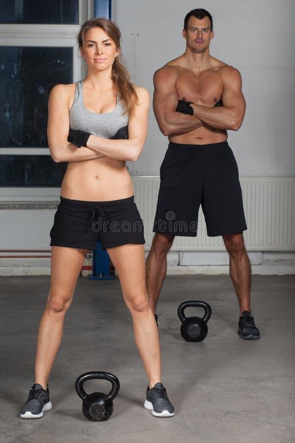 Man en vrouw met ketelklok in een gymnastiek stock foto's