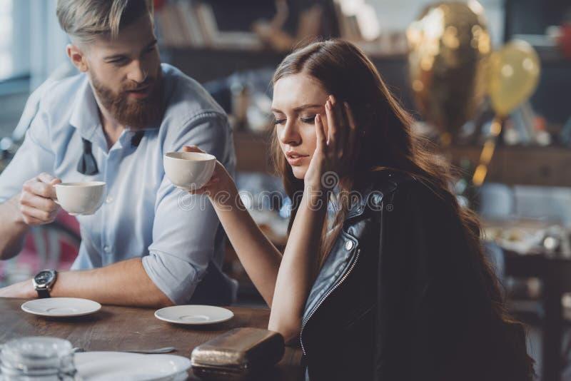 Man en vrouw met koffie in slordige ruimte stock afbeeldingen