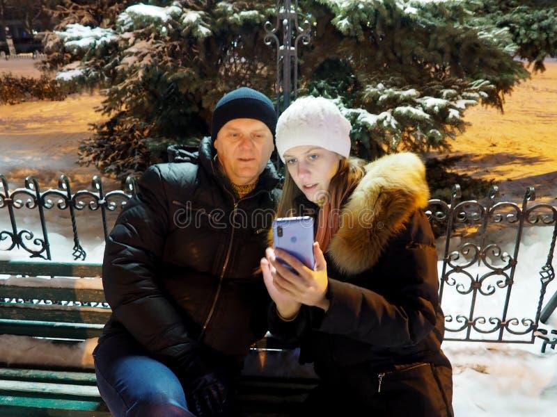 Man en vrouw op een bank in de Winterpark in de avond royalty-vrije stock foto's