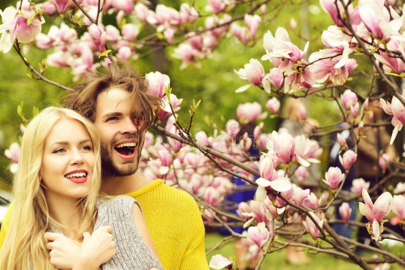 Man en vrouw, paar in liefde in de bloemen van de de lentemagnolia stock foto