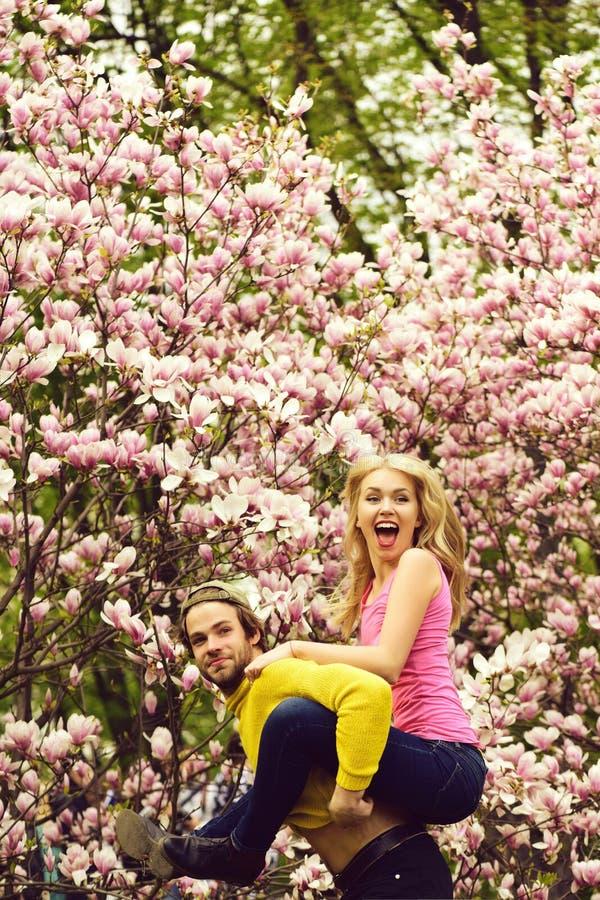 Man en vrouw, paar in liefde in de bloemen van de de lentemagnolia stock fotografie
