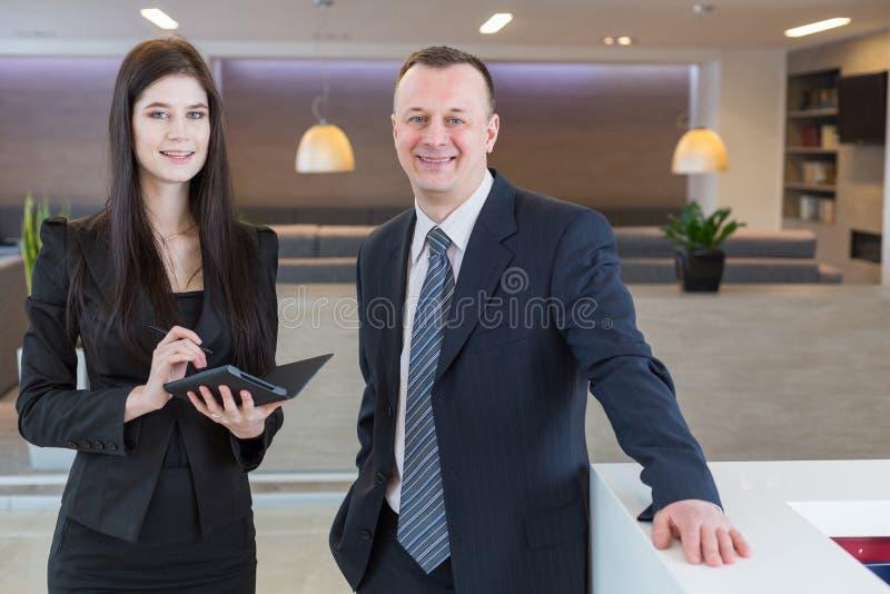 Man en vrouw in pakken die zich bij de ontvangst bevinden stock foto's