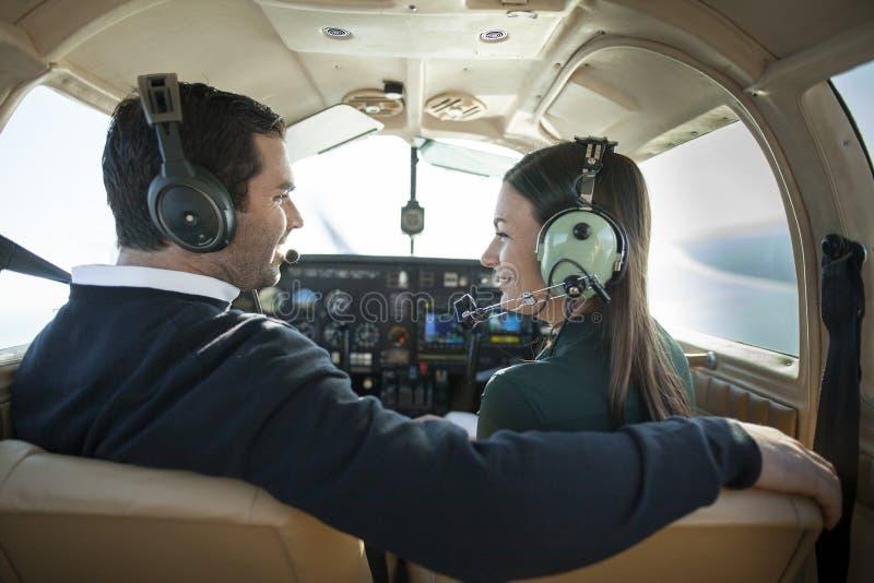 Man en vrouw in privé vliegtuig stock afbeeldingen
