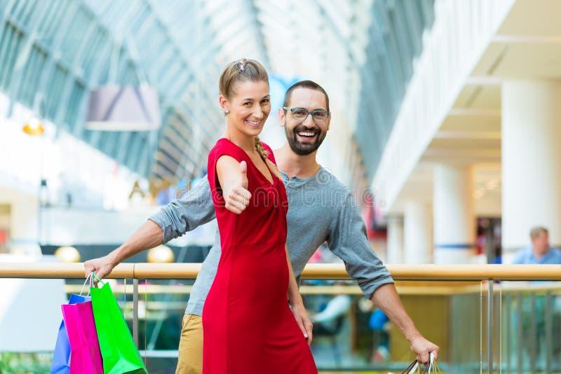 Man en vrouw in winkelcomplex met zakken stock fotografie