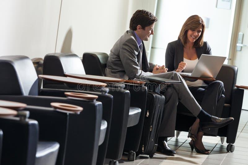 Man en Vrouwen Commerciële Vergadering met Laptop bij Luchthaven royalty-vrije stock fotografie