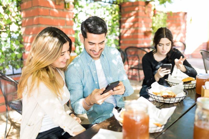 Man en Vrouwen die Mobiele Telefoons met behulp van bij Hamburgerwinkel stock fotografie
