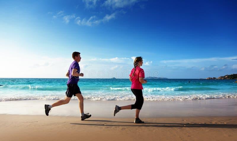 Man en vrouwen die op tropisch strand lopen stock foto