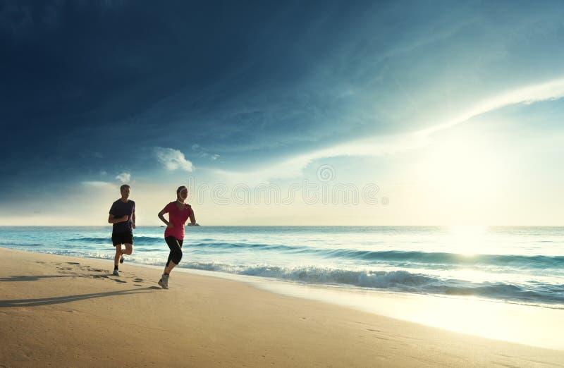 Man en vrouwen die op tropisch strand lopen stock fotografie