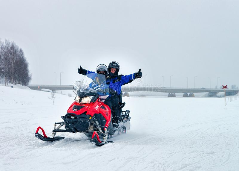 Man en vrouwen het berijden sneeuwscooter in de winter Rovaniemi stock afbeeldingen