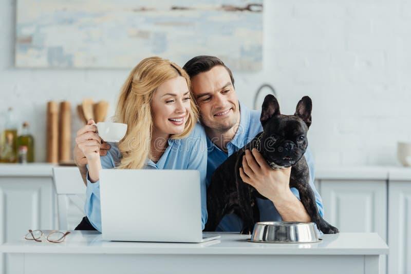 Man en vrouwen het drinken koffie en het koesteren van hun hond op keukenlijst royalty-vrije stock foto's