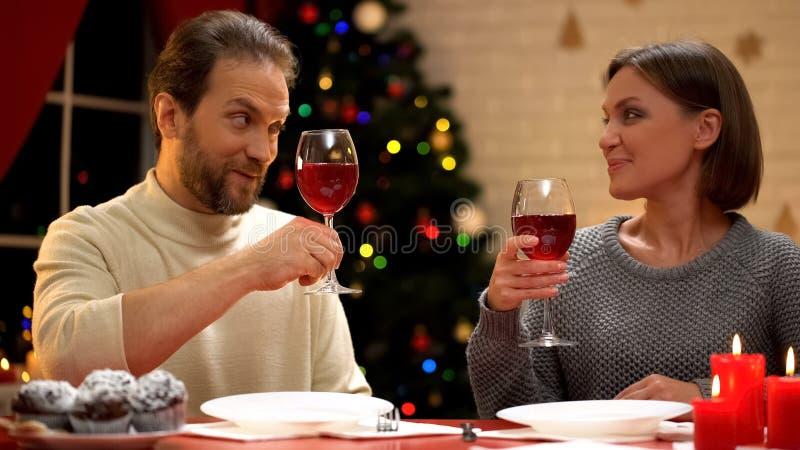 Man en vrouwen het drinken wijn op Kerstmisvooravond, het mannelijke flirten, verhouding royalty-vrije stock foto's