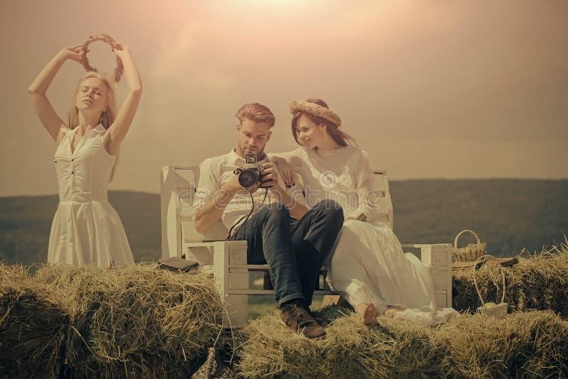 Man en vrouwen het letten op foto's in camera op bank stock foto's