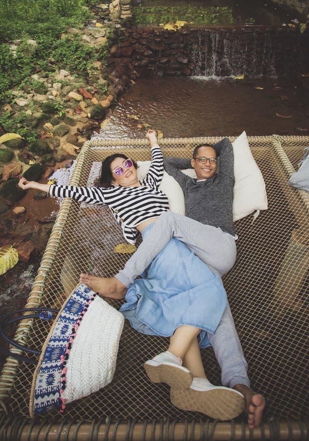 Man en vrouwen het ontspannen met gelukemotie op netto wieg over stromende kreek stock foto's