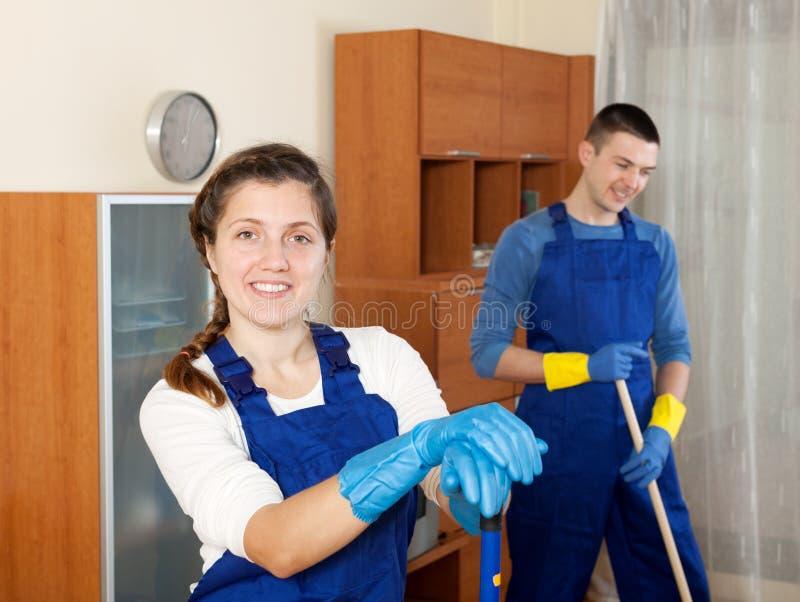 Man en vrouwen het schoonmaken in ruimte stock afbeelding