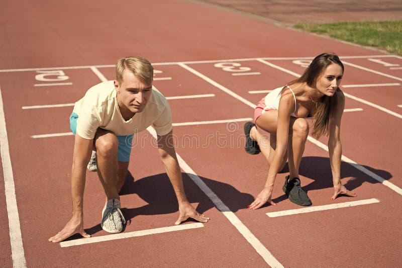 Man en vrouwen laag de lopende oppervlaktestadion van de beginpositie Lopend de concurrentie of geslachtsras De snellere sportman royalty-vrije stock foto's