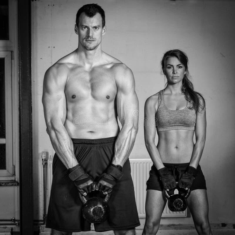 Man en vrouwen opheffende ketelklok crossfit stock afbeelding