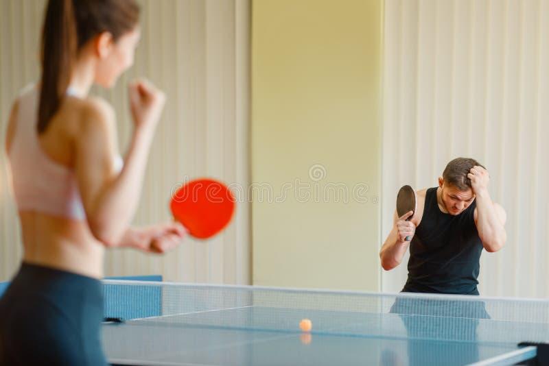Man en vrouwen speelpingpong, meisjeswinnaar royalty-vrije stock afbeelding