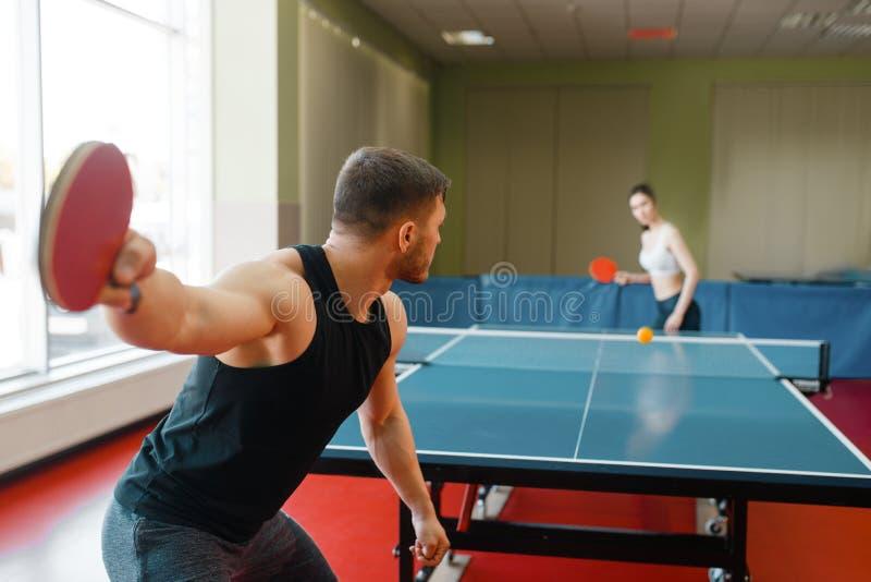 Man en vrouwen speelpingpong, nadruk op racket stock afbeelding