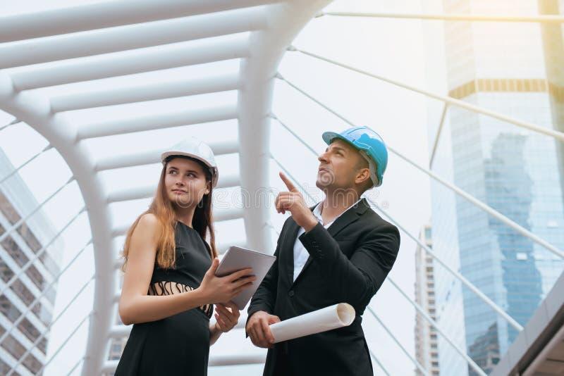 Man en vrouwen starten de industriële ingenieurs een tablet en blauwdrukken houden die werkend en op bouwterrein bespreken, nieuw royalty-vrije stock foto