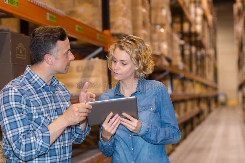 Man en vrouwenarbeider met tablet bij pakhuis royalty-vrije stock afbeelding