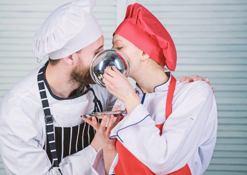 Man en vrouwenchef-kok in restaurant achter metaaldienblad Geheim ingredi?nt door recept Eenvormige kok Familie die binnen kookt royalty-vrije stock afbeelding