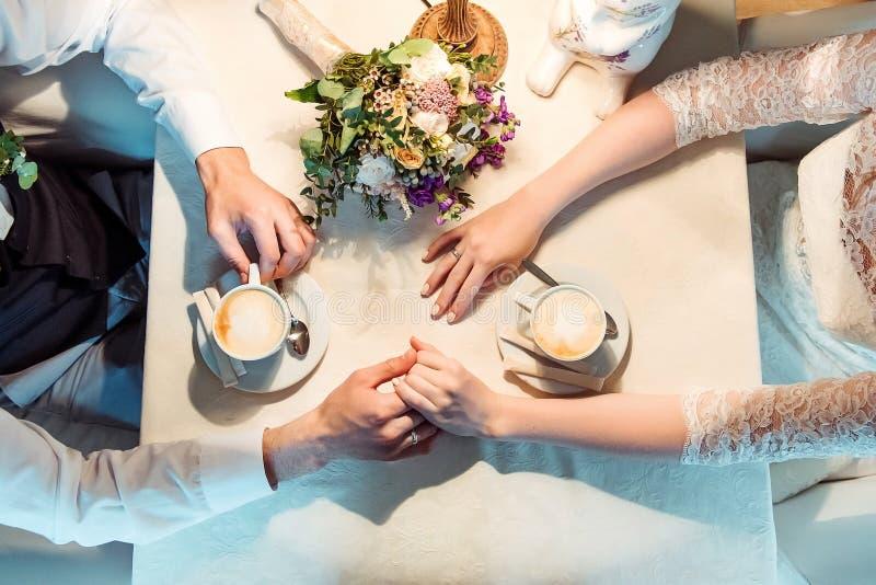 Man en vrouwenhanden en koffiekoppen op de lijst stock foto