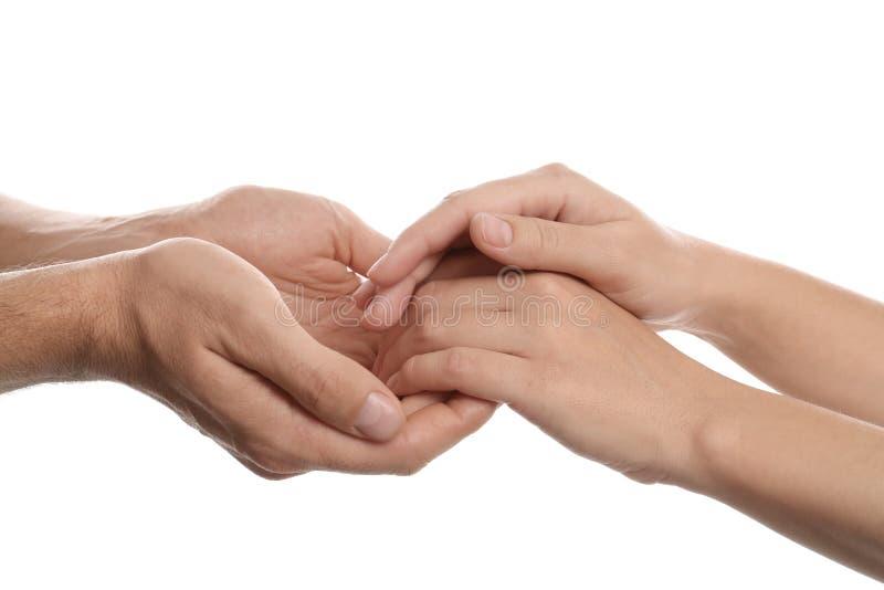 Man en vrouwenholdingshanden op wit, close-up Hulp en steunconcept stock afbeelding