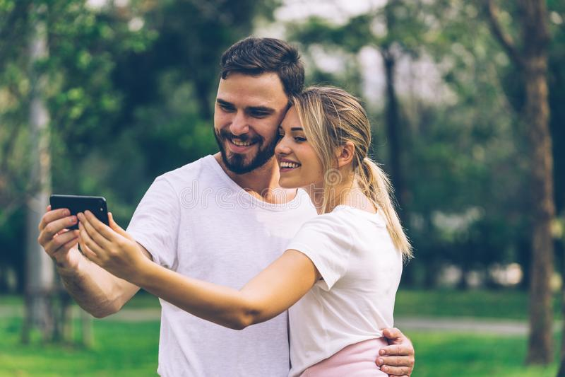 Man en Vrouwenminnaar selfie samen in openbaar park stock afbeelding