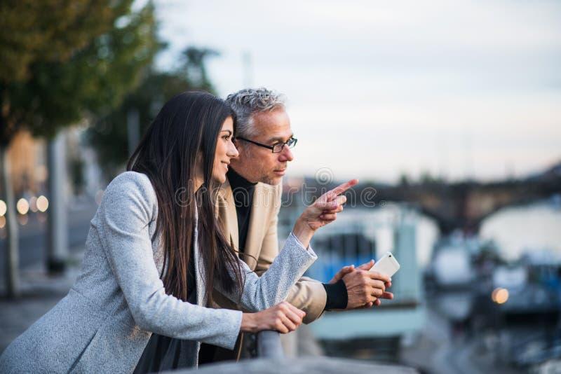 Man en vrouwenpartners die zich door een rivier in stad van Praag bevinden stock afbeelding