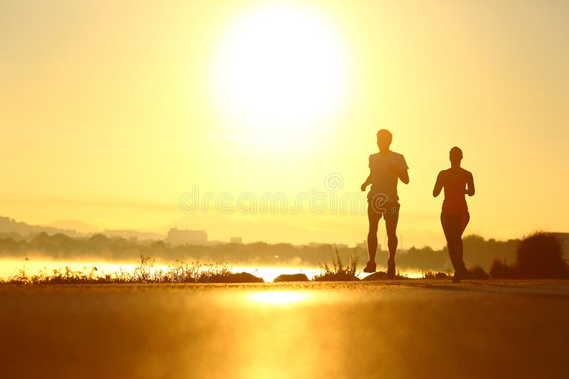 Man en vrouwensilhouetten die bij zonsopgang lopen stock foto