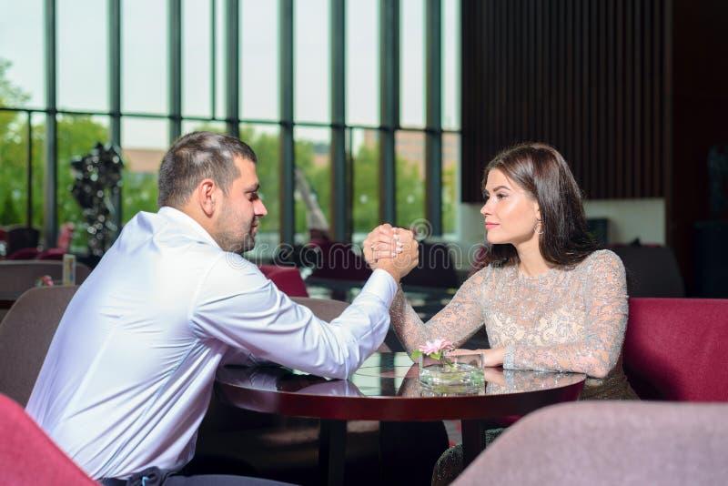 Man en vrouwenstrijd op hun handen stock afbeelding