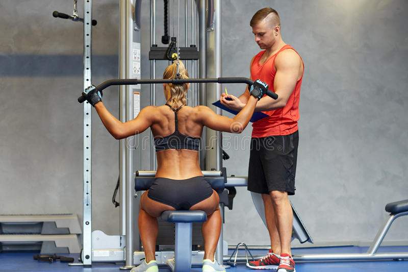 Man en vrouwenverbuigingsspieren op gymnastiekmachine royalty-vrije stock afbeelding