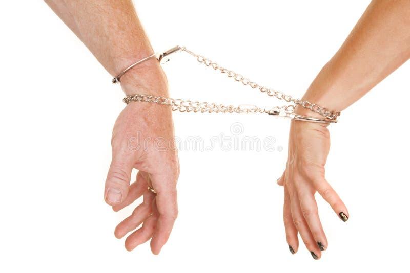 Man en vrouwenwapenshandcuffs handen neer stock fotografie