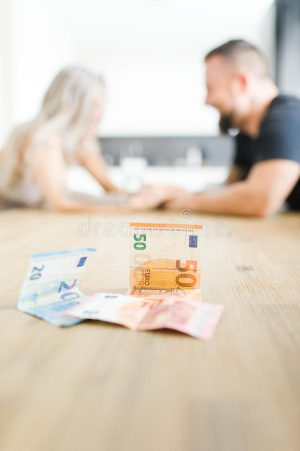 Man en vrouwenzitting door lijst aangaande overkant en het stellen van financi?le problemen royalty-vrije stock fotografie
