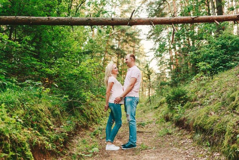 Man en zwangere vrouw in het bos stock afbeeldingen