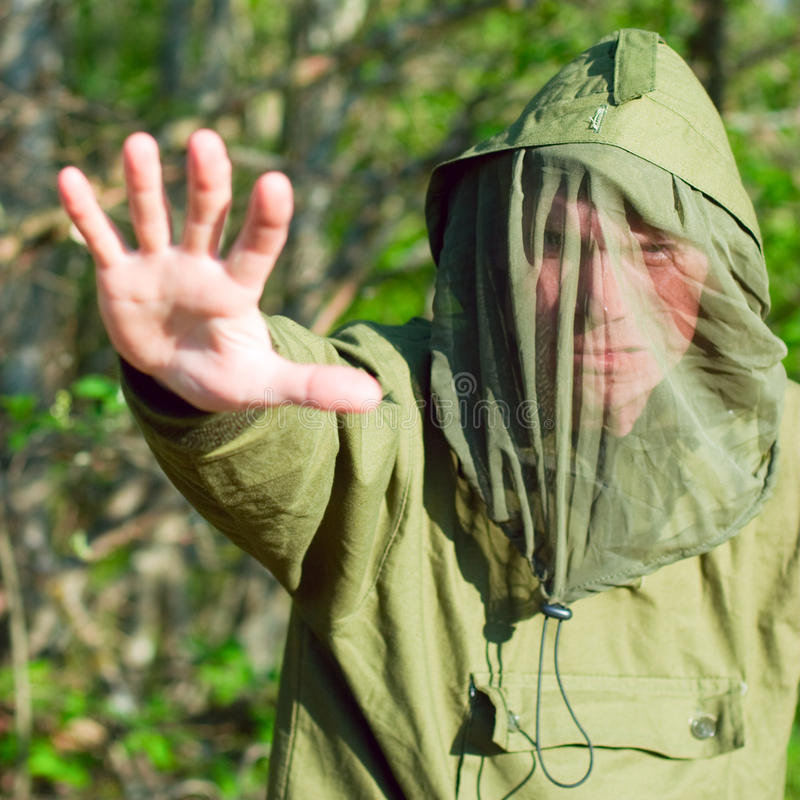 Man in encephalitis protective clothing. Man wearing encephalitis protective clothing hold up his hand outdoors, shallow DOF royalty free stock image