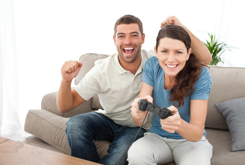 Man Encouraging His Girlfriend Playing Video Game Stock Photography
