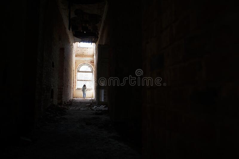 A man at the end of a dark corridor inside an abandoned building. An intimidating view inside a ghostly building royalty free stock photo