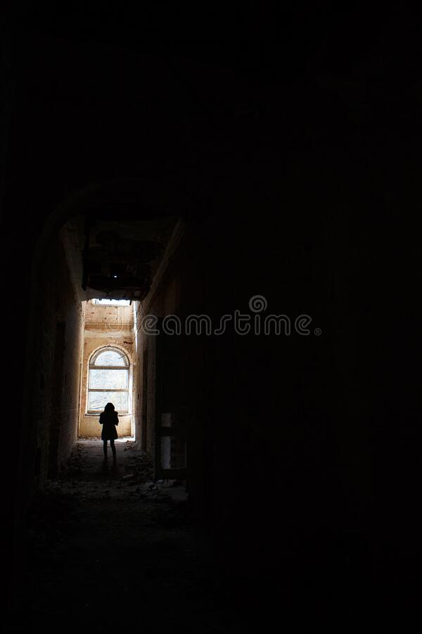 A man at the end of a dark corridor inside an abandoned building. An intimidating view inside a ghostly building stock images