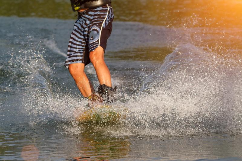 A man engaged in wakeboard on the lake performs jumps royalty free stock photography
