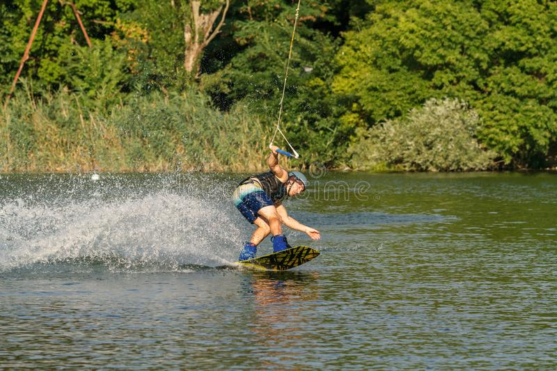 A man engaged in wakeboard on the lake performs jumps royalty free stock images