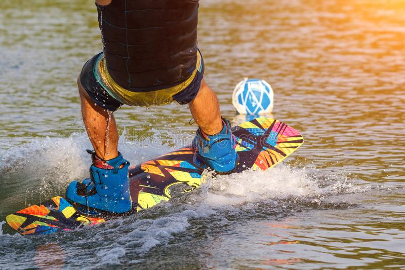 A man engaged in wakeboard on the lake performs jumps royalty free stock photo