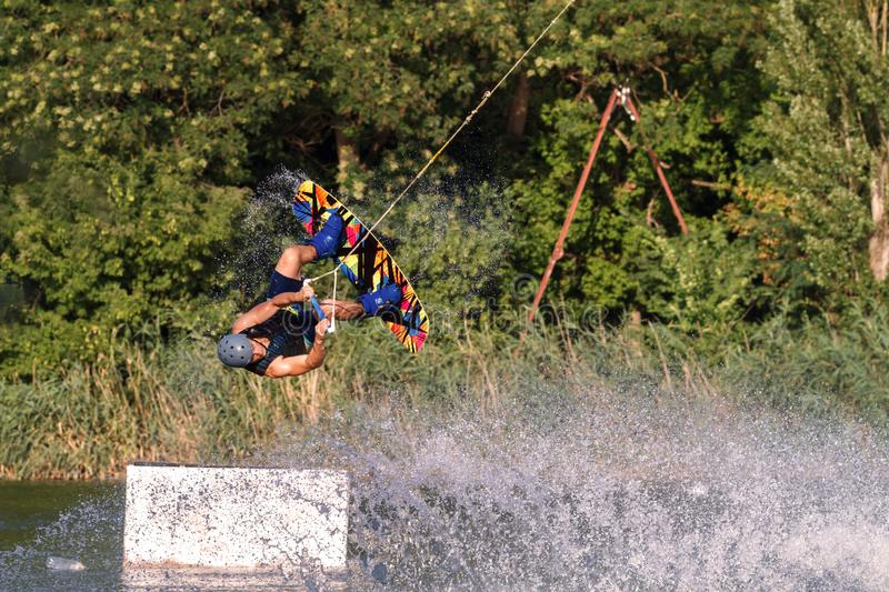 A man engaged in wakeboard on the lake performs jumps royalty free stock image