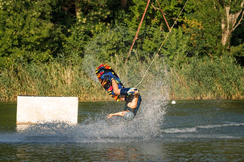 A man engaged in wakeboard on the lake performs jumps royalty free stock photos