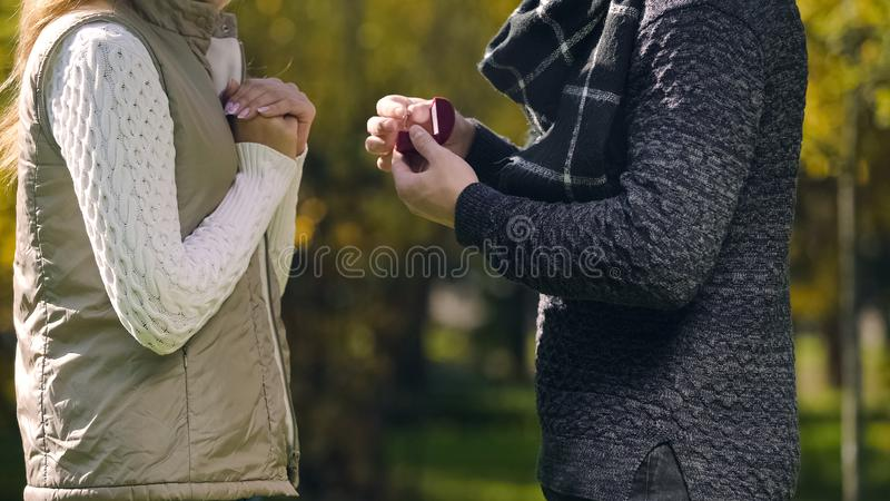 Man with engagement ring asking woman to marry him in autumn park, surprise stock photos